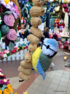 Knitted blue tit and peanuts pergola